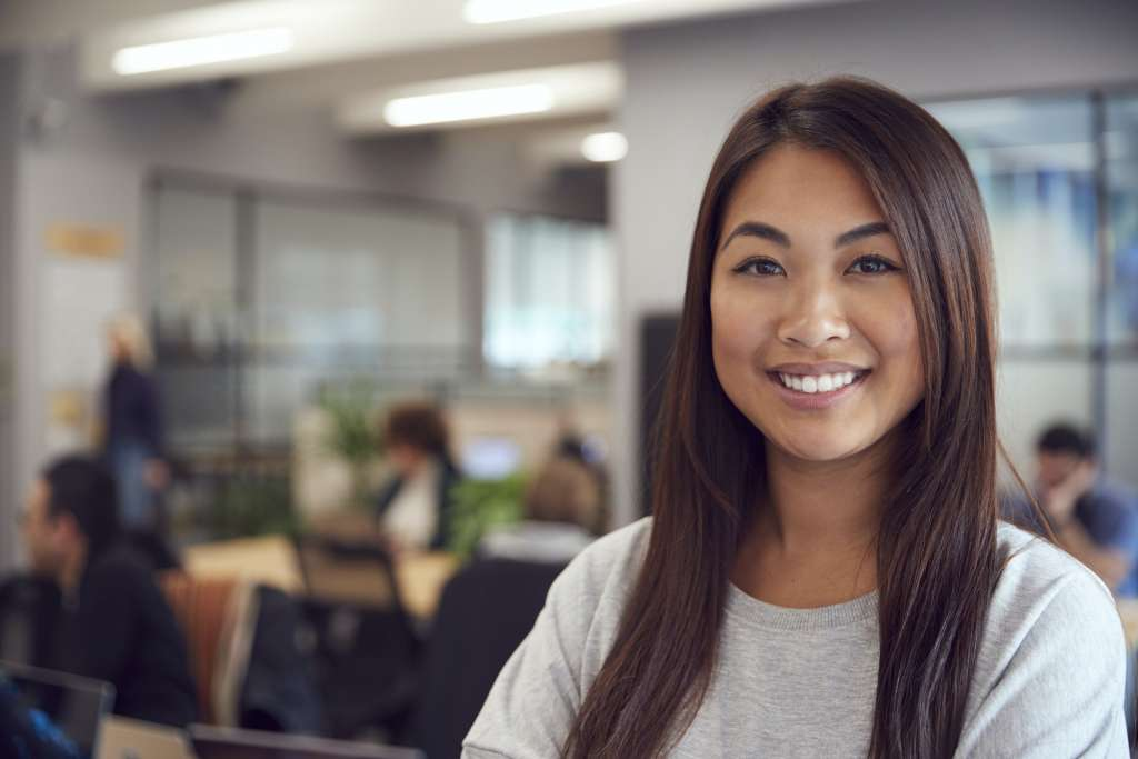 Head And Shoulders Portrait Of Smiling Young Asian Businesswoman Working In Busy Modern Office